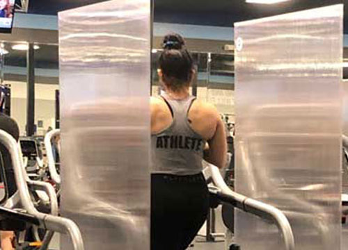 woman working out between two protection shields